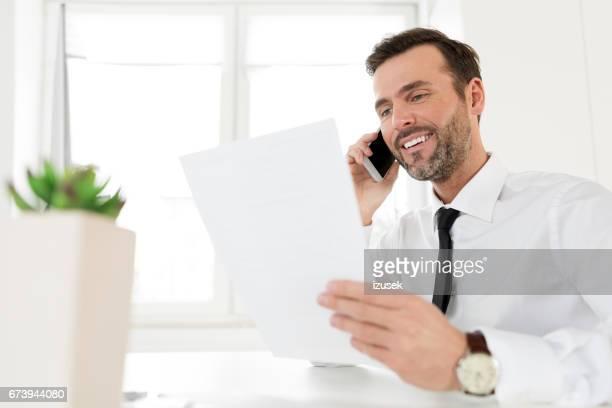 empresário bem sucedido, falando no telefone em seu escritório - izusek - fotografias e filmes do acervo
