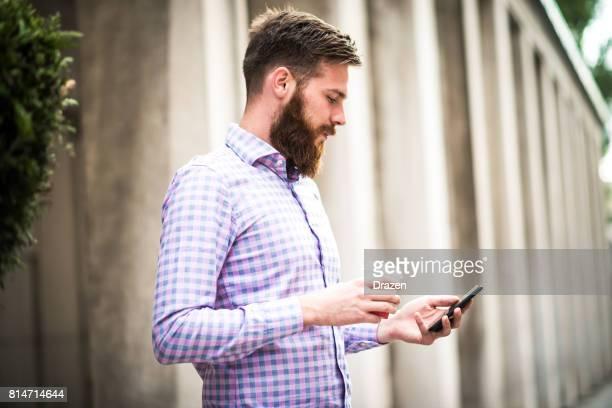 Erfolgreicher Geschäftsmann mit Bart mit Smartphone