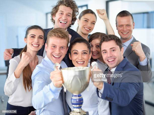 Successful businesspeople celebrating with the cup in hands