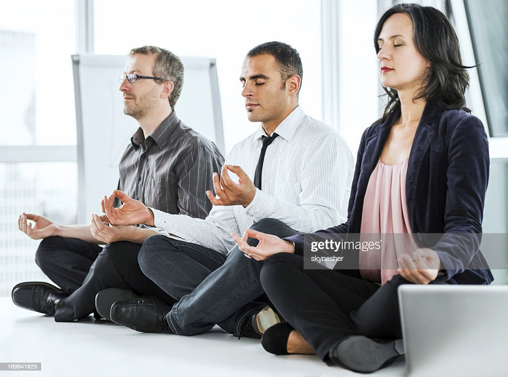 Successful businesspeople meditating in the office. : Stock Photo