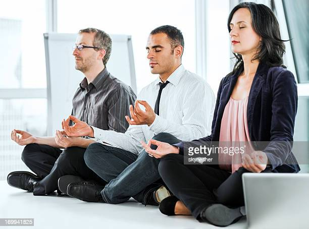 Successful businesspeople meditating in the office.