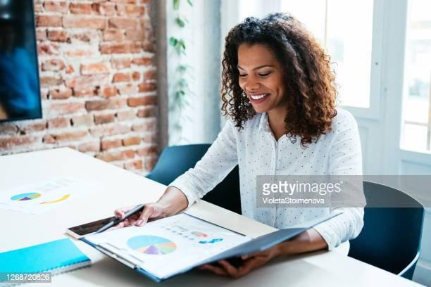 職場で財務報告書を分析する成功したビジネスウーマン。 - 報告書 ストックフォトと画像