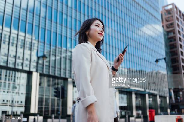 successful businesswoman looking away while using smart phone - asian and indian ethnicities stock pictures, royalty-free photos & images