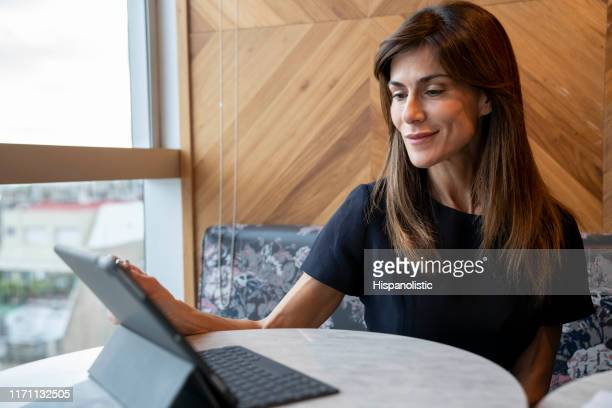 Successful businesswoman looking very satisfied while working with a tablet at a coworking office