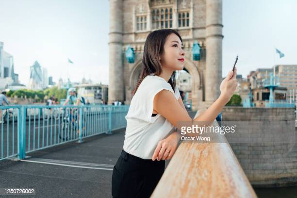 successful businesswoman on the go with smartphone in the city - finding stock pictures, royalty-free photos & images