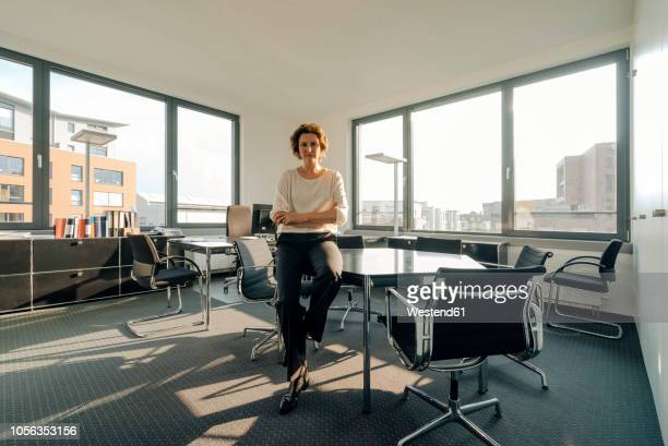 successful businesswoman sitting on desk in her office with arms crossed - direttrice foto e immagini stock
