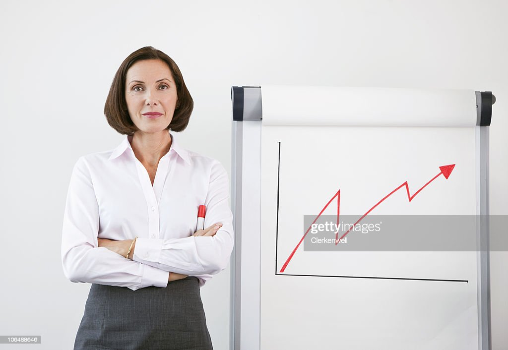 Successful businesswoman standing by line graph : Bildbanksbilder