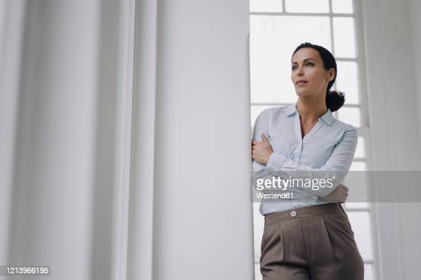 successful businesswoman, standing by window, leaning on wall, thinking - cabelo preto imagens e fotografias de stock