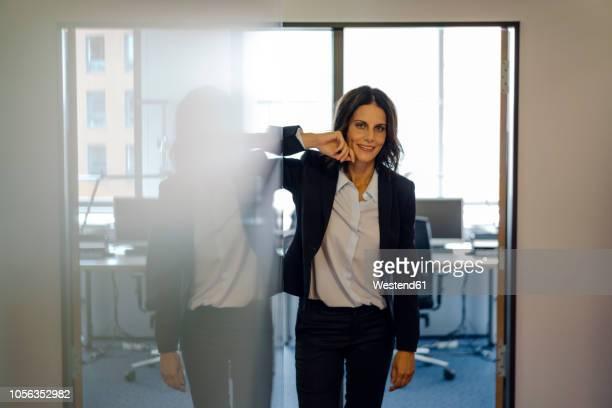 Successful businesswoman standing in office door, smiling