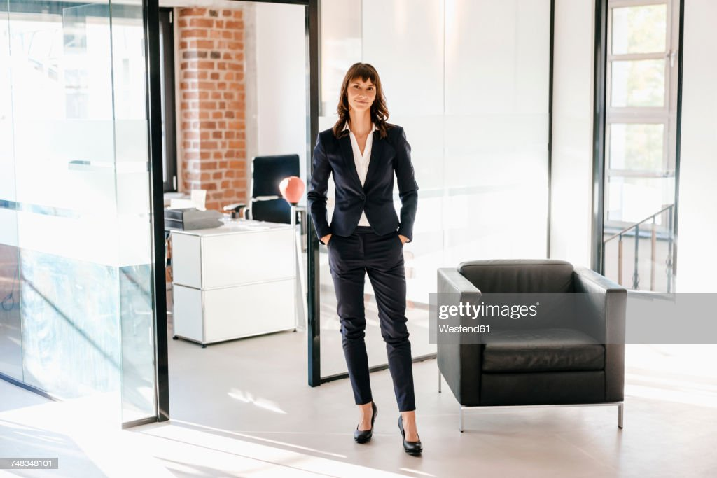 Successful businesswoman standing in office with hands in pockets : Stock-Foto
