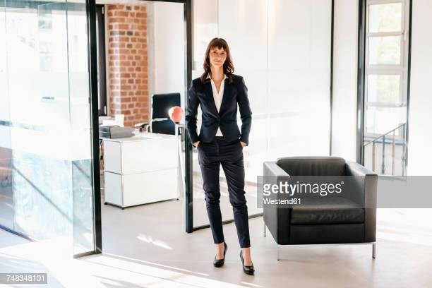 successful businesswoman standing in office with hands in pockets - ganzkörperansicht stock-fotos und bilder