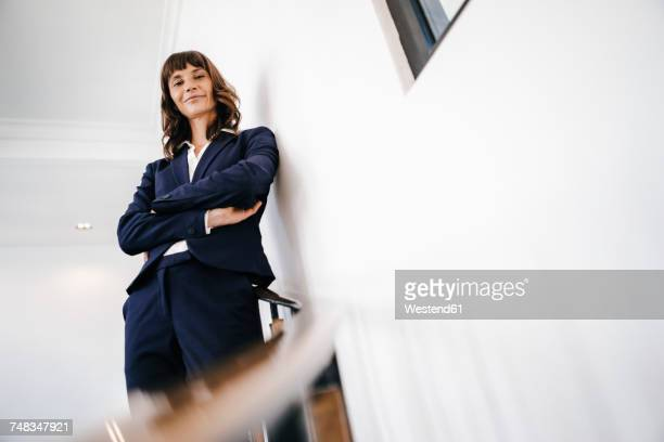 successful businesswoman standing on staircase - low angle view stock pictures, royalty-free photos & images
