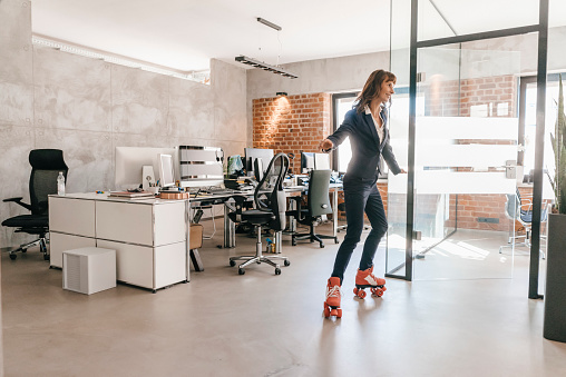 Successful businesswoman wearing roller skates in office - gettyimageskorea