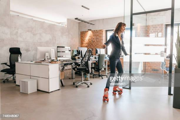 Successful businesswoman wearing roller skates in office
