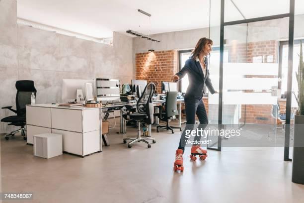successful businesswoman wearing roller skates in office - patinação esporte - fotografias e filmes do acervo