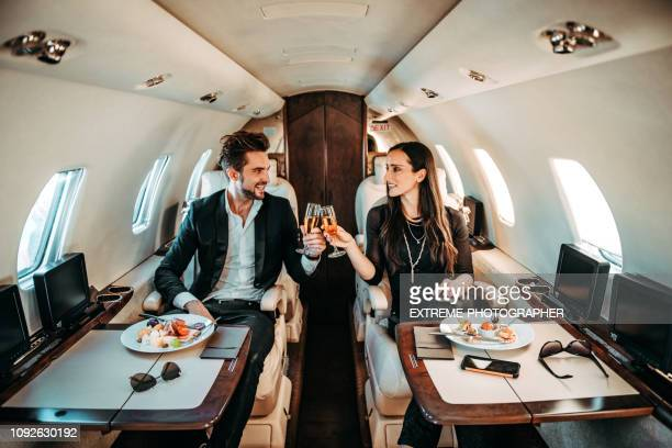 successful couple making a toast with champagne glasses while having canapes aboard a private airplane - ricchezza foto e immagini stock