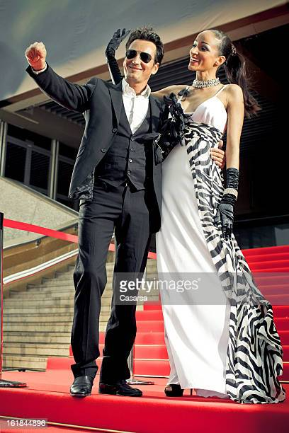 successful couple on red carpet - fete stock photos and pictures