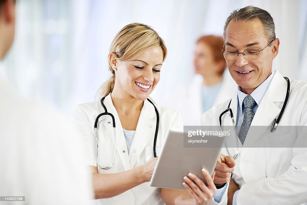 Successful doctors using together a touchpad. : Stock Photo