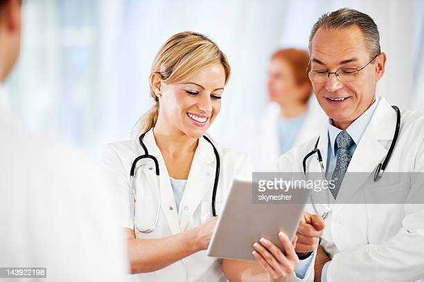 Successful doctors using together a touchpad.