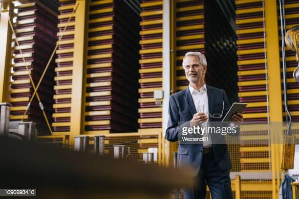 successful entrepreneur standing in his company, using digital tablet - verantwortung stock-fotos und bilder