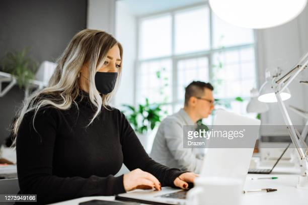 successful entrepreneurs working in the office with face masks, keeping social distance - hot desking stock pictures, royalty-free photos & images