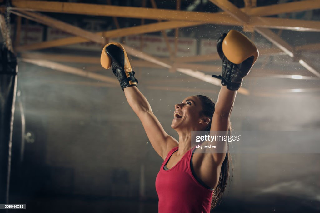 Successful female boxer celebrating her victory in a health club. : Stock Photo