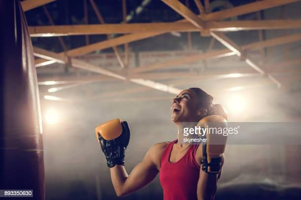 Erfolgreiche Boxerin feiert ihren Sieg in einem Fitnessstudio.