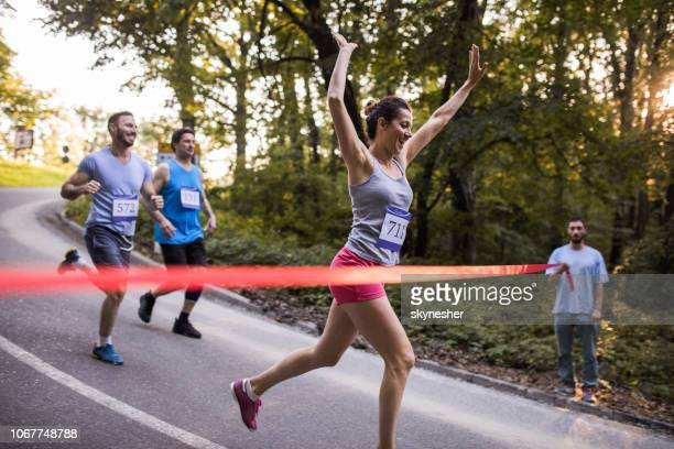 successful female marathon runner crossing finish line in nature. - finishing line stock pictures, royalty-free photos & images