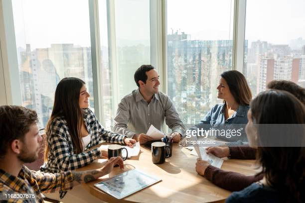 successful group of people discussing business at the office all looking very cheerful - hispanolistic stock photos and pictures