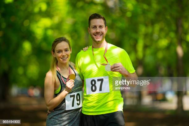 successful happy couple with medals after marathon run - second place stock pictures, royalty-free photos & images