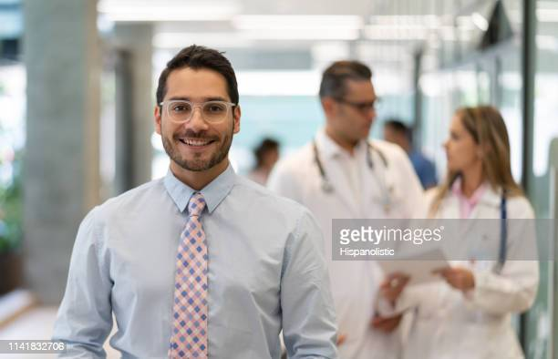 successful hospital supervisor looking at camera smiling - director stock pictures, royalty-free photos & images