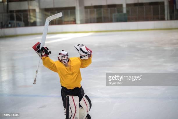 Réussie hockey sur glace célébrant la victoire avec les bras levés.