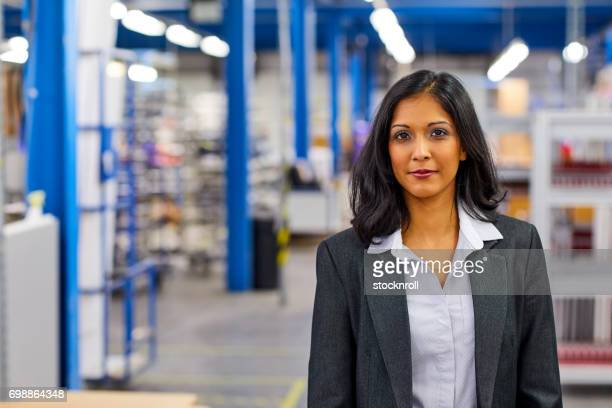 Successful indian female entrepreneur standing in factory