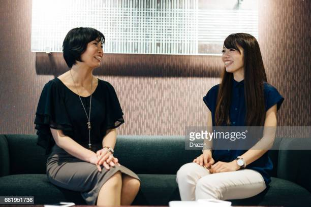 Successful Japanese businesswomen having meeting, discussing projects and cooperation