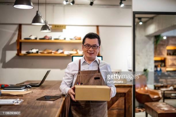 成功した男性台湾の靴商人靴箱 - シューズボックス ストックフォトと画像