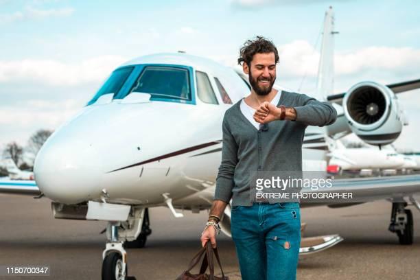 erfolgreicher mann, der die zeit überprüft, während er von einem privatflugzeug entfernt ist, das auf einem taxistand geparkt ist - armbanduhr stock-fotos und bilder