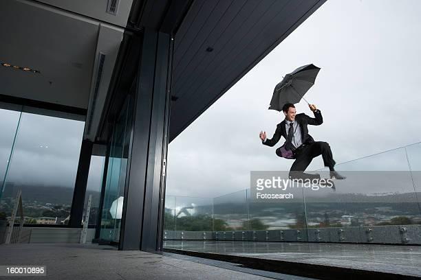 Successful man jumping in the rain