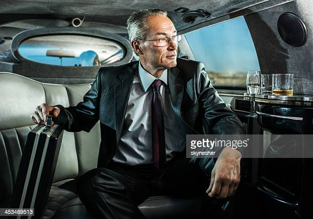 Successful man on a business travel in limousine.