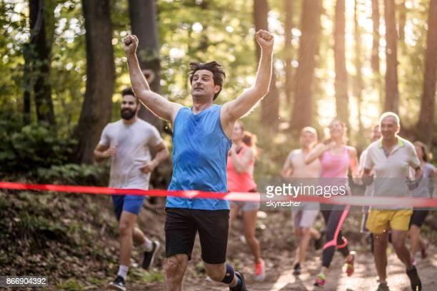 Erfolgreicher Mann läuft durch die Ziellinie und feiern Sieg mit seiner erhobenen Armen.