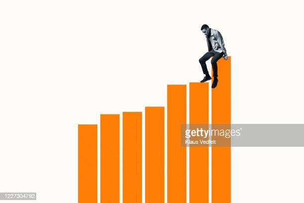 successful man sitting on top of orange bar graph - balkendiagramm stock-fotos und bilder