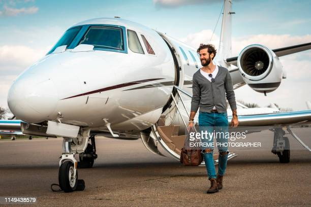 successful man walking away from a private airplane parked on an airport taxiway - private aeroplane stock pictures, royalty-free photos & images