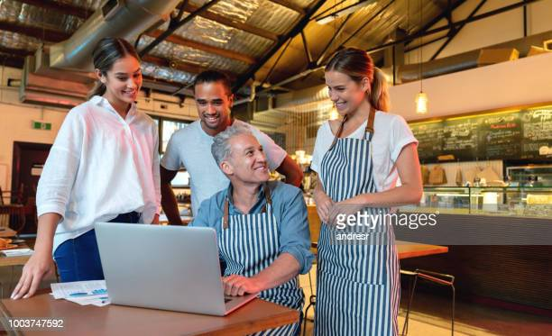 successful manager talking to the staff at a restaurant - restaurant manager stock pictures, royalty-free photos & images