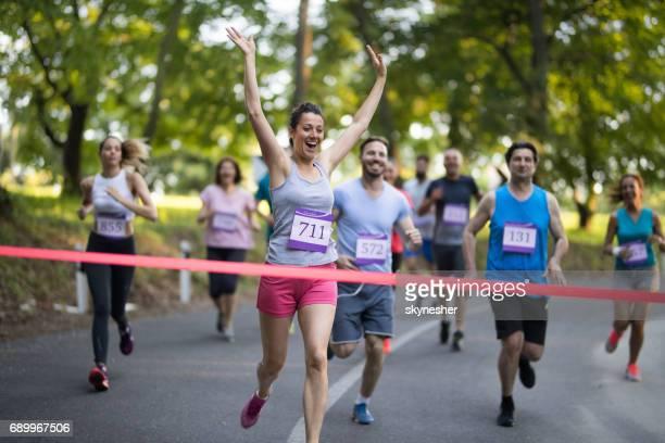 Erfolgreiche Marathonläufer überqueren der Ziellinie mit erhobenen Armen.