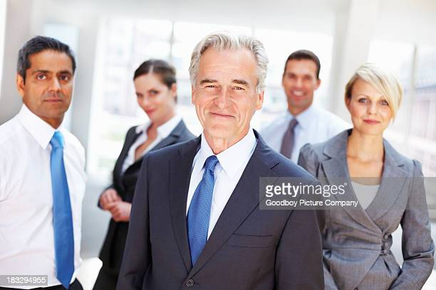 Successful mature business man with his team in background