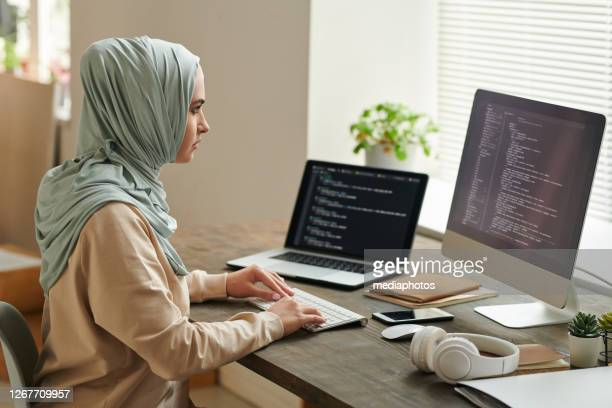successful middle eastern woman wearing light blue hijab sitting at desk working on computer code, copy space - programmer stock pictures, royalty-free photos & images