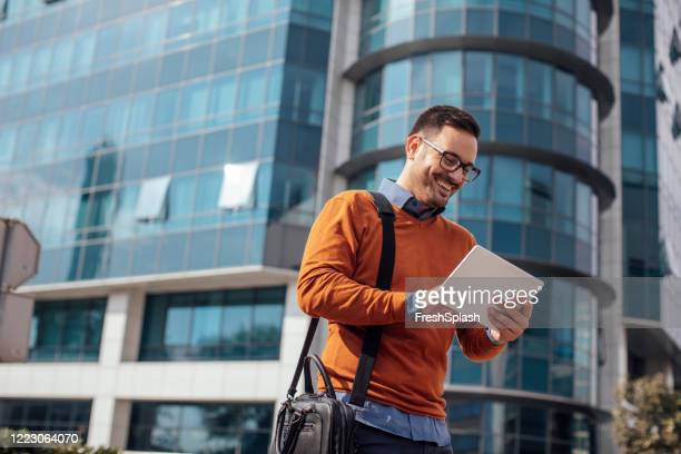 successful modern young businessman using a digital tablet on the street - on the move stock pictures, royalty-free photos & images