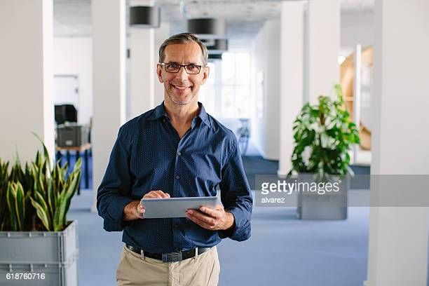 successful senior businessman standing in office - directeur stockfoto's en -beelden