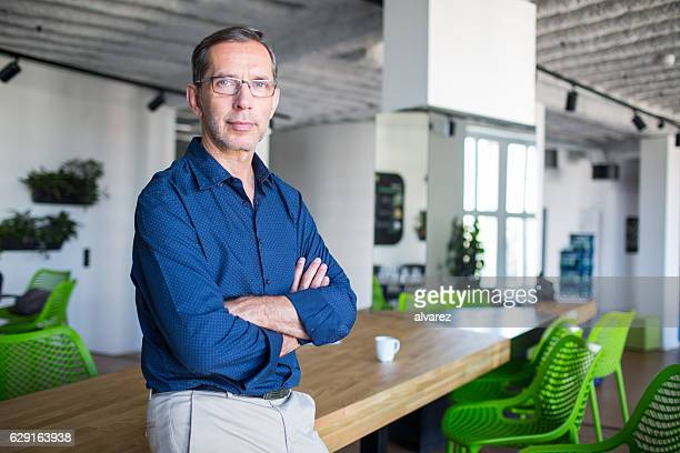 successful senior businessman standing in office - bold man stock photos and pictures