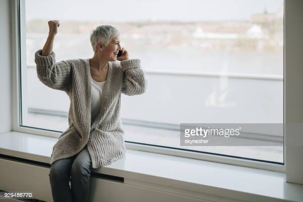 successful senior woman sitting by the window and talking on cell phone. - good news stock pictures, royalty-free photos & images