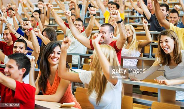 Successful students sitting with raised arms